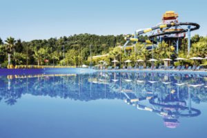 Hotel pool with reflection of waterpark slides and trees